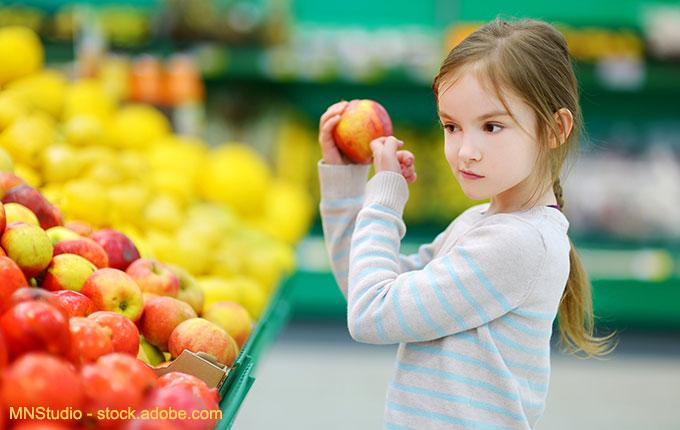 Kind überprüft Obst beim Einkauf
